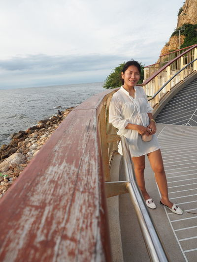 Portrait of woman standing on railing by sea against sky