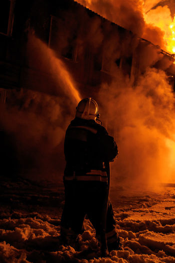 Firefighter spraying water on burning fire at night