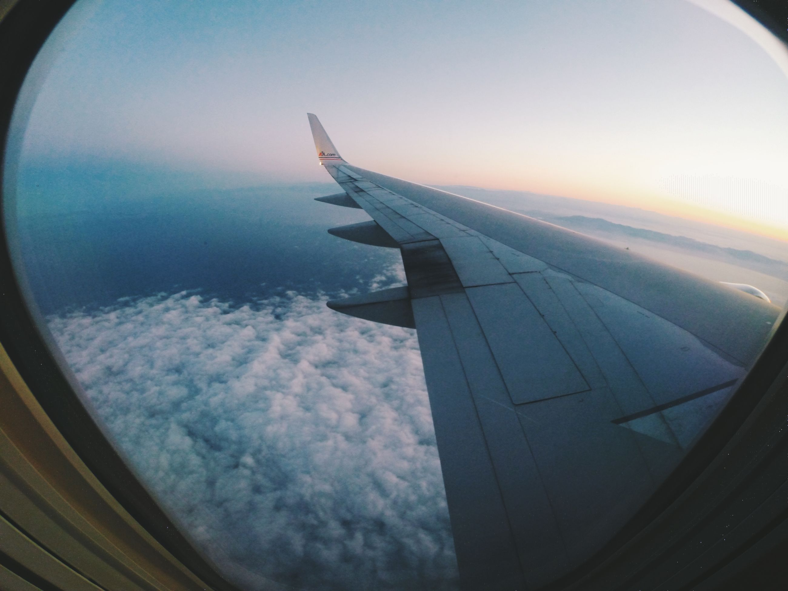 airplane, aircraft wing, transportation, air vehicle, flying, mode of transport, part of, cropped, sky, aerial view, travel, mid-air, public transportation, journey, cloud - sky, on the move, window, glass - material, vehicle interior, airplane wing