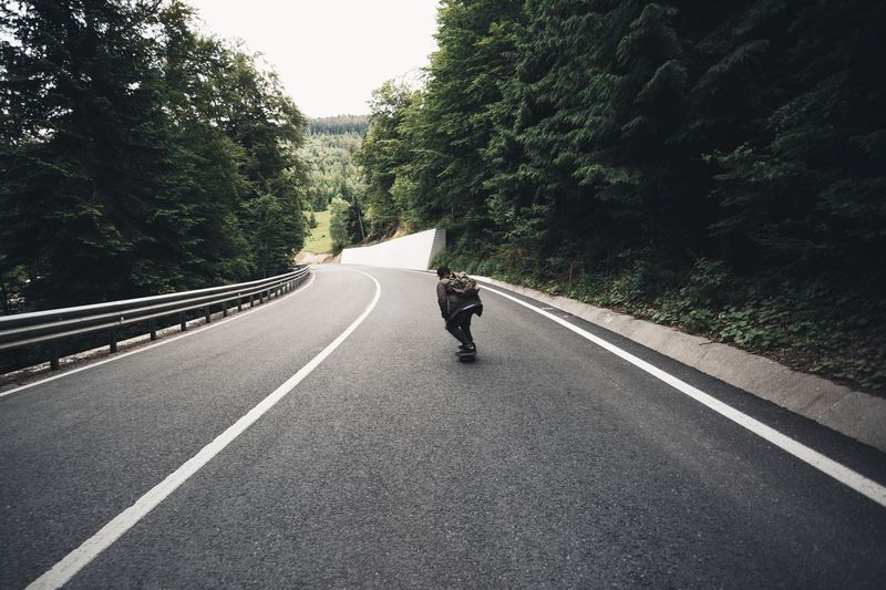 Man on road amidst trees