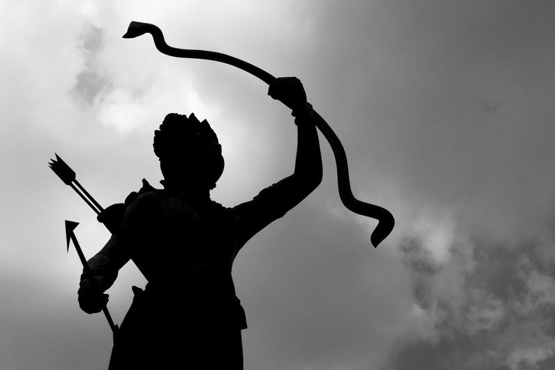 Low Angle View Of Silhouette Statue Against Cloudy Sky