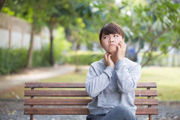 Young woman scratching cheek while sitting on bench at park