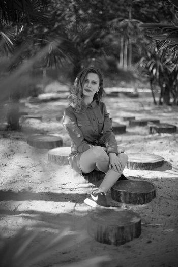 Portrait of woman sitting on tree
