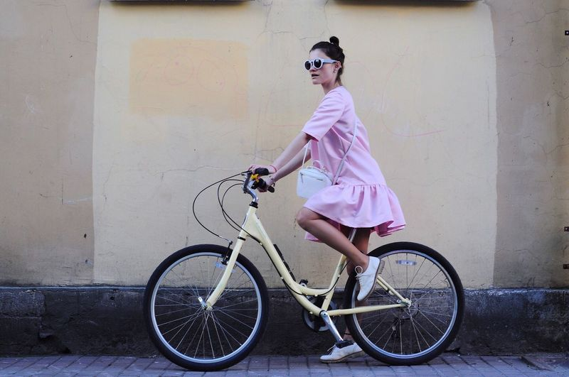 Full length of woman cycling on road by wall