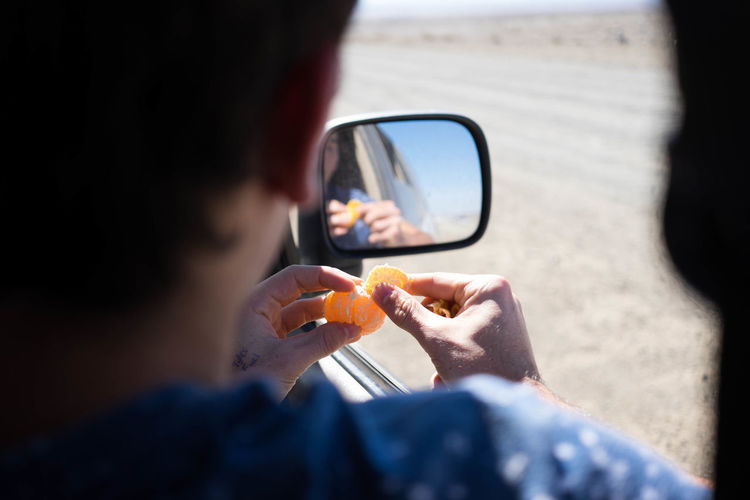 Cropped image of man peeling orange while sitting in car by reflection on side-view mirror