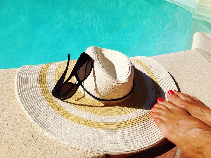 Low Section Of Woman By Hat And Sunglass At Poolside