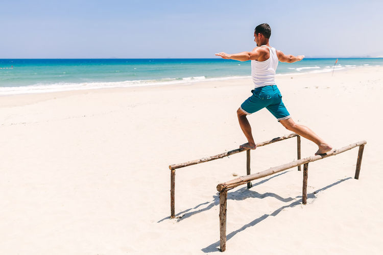 Man training and workout on beach. Fitness outdoors. Beach One Person Sand Sea Ocean Fitness Fitness Training Outdoors Man Males  Strong Yoga Stretching Workout Sport Leisure Activity Lifestyles Relaxing Exercising Sky Day Water Horizon Over Water