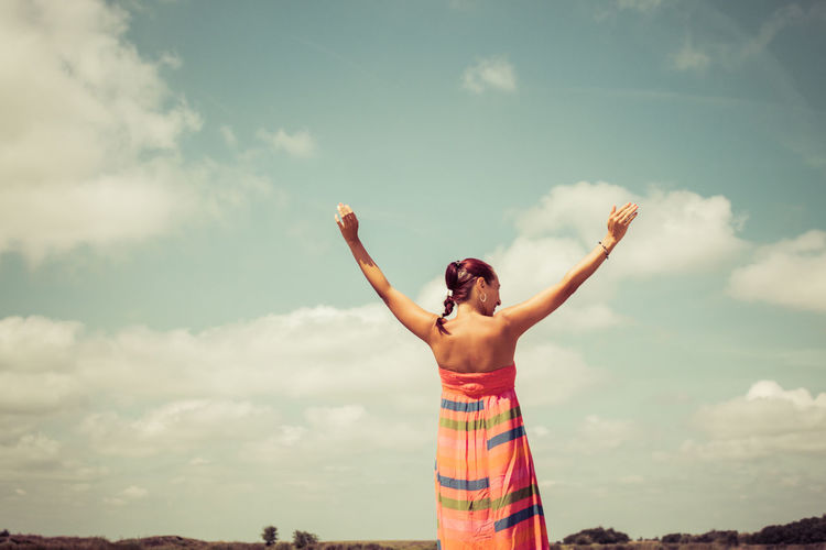 Rear view of carefree woman with arms outstretched against the sky. copy space.
