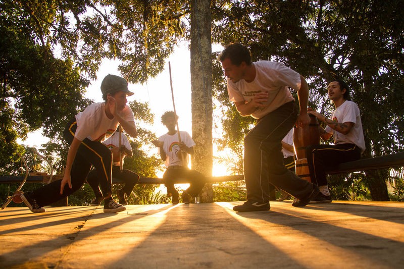 capoeira de Angola Playing Boys Sunlight Capoeira Sudamerica Capoeirabrasil Capoeira Angola Tree Leisure Activity Real People Togetherness Lifestyles Plant Nature People Positive Emotion Men Emotion Group Of People Child Shadow Women Full Length Casual Clothing Enjoyment Friendship Outdoors