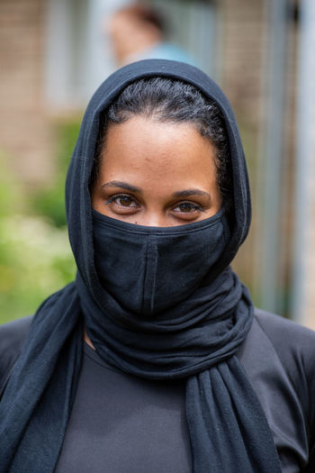 Close-up portrait of young woman wearing mask outdoors