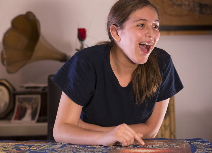 Happy teenage girl playing puzzle at home