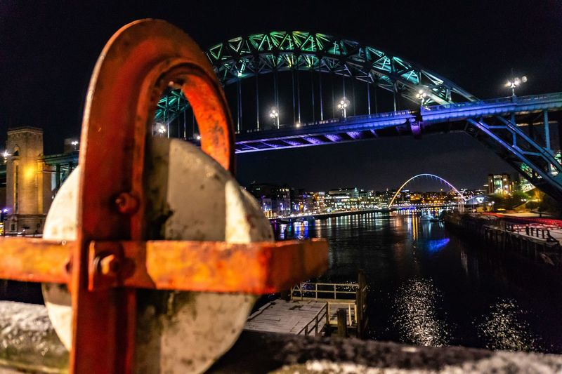 Low angle view of illuminated bridge over river in city at night