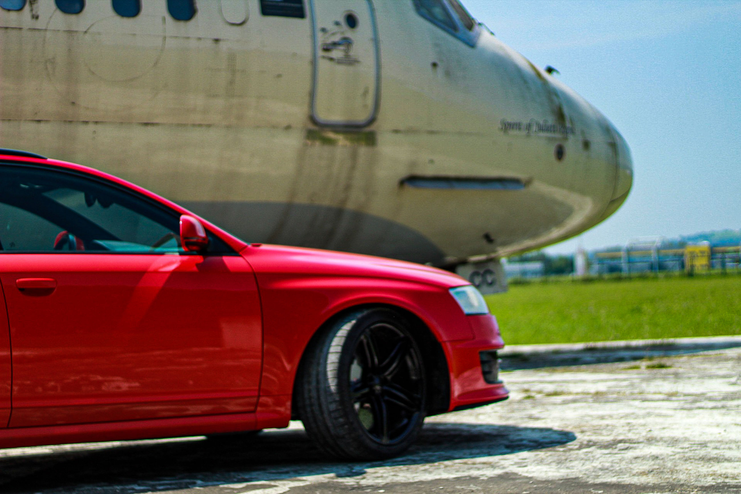 transportation, mode of transportation, motor vehicle, car, red, land vehicle, day, no people, stationary, nature, travel, outdoors, city, road, motion, on the move, airport runway, focus on foreground, sky, reflection, wheel