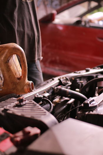 Close-up of man oiling car