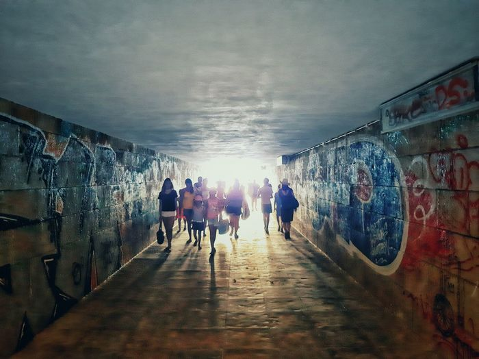 Group of people walking in tunnel