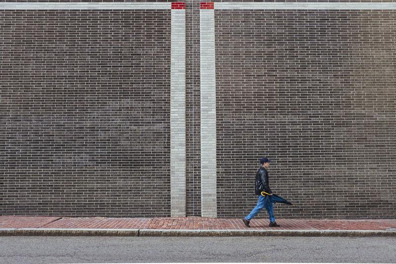 Side view of man walking on sidewalk