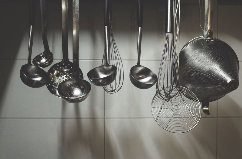 Utensils hanging against wall in kitchen at home