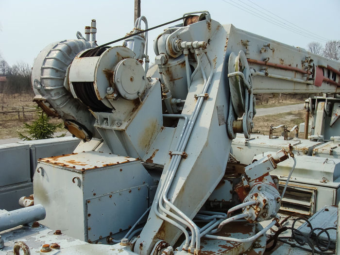 Close-up of abandoned machinery on field against sky