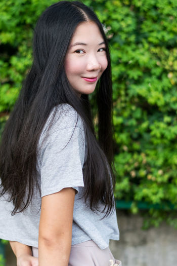 Smiling beautiful Asian girl from behind shot Long Hair Hair Looking At Camera Hairstyle Portrait Smiling Real People One Person Women Casual Clothing Focus On Foreground Leisure Activity Lifestyles Side View Black Hair Young Adult Happiness Beauty Beautiful Woman Teenager Outdoors Behind Asian  Happiness Model Pose