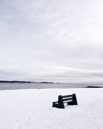 Empty bench on snowed landscape