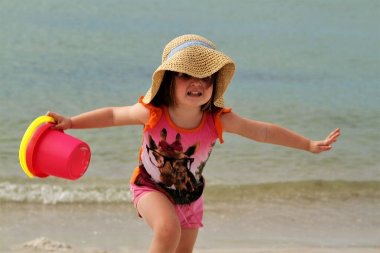 Little girl running like a bird with outstreched arms Beach Water Land One Person Sea Hat Leisure Activity Childhood Real People Lifestyles Clothing Day Nature Child Focus On Foreground Girls Sand Pink Color Outdoors Sun Hat Innocence