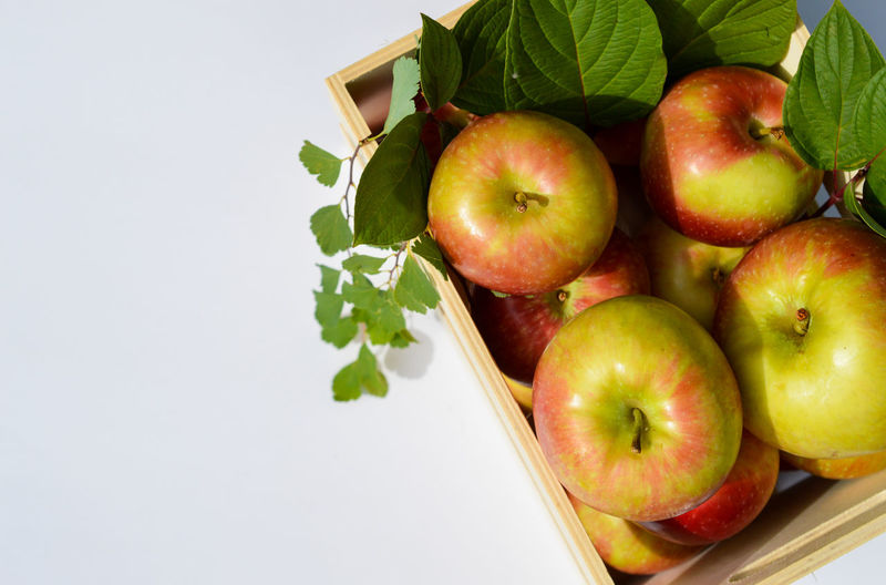 Close-up of apples and fruits on table against white background