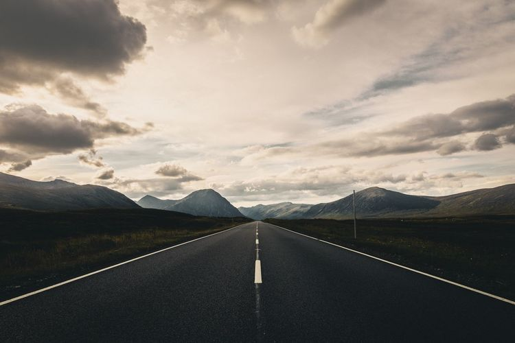 Empty Road Leading Towards Mountains Against Sky