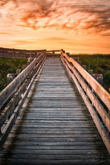 Boardwalk leading towards sea against sky during sunset