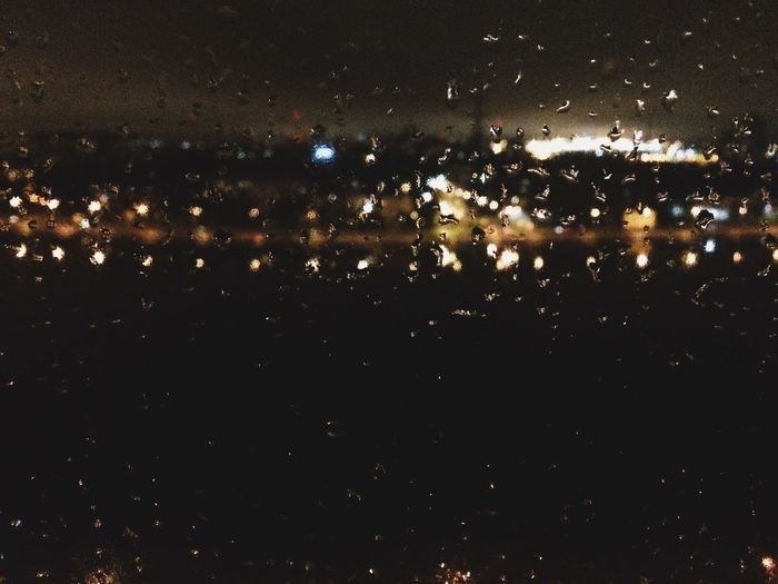 Close-up of wet illuminated lights against sky