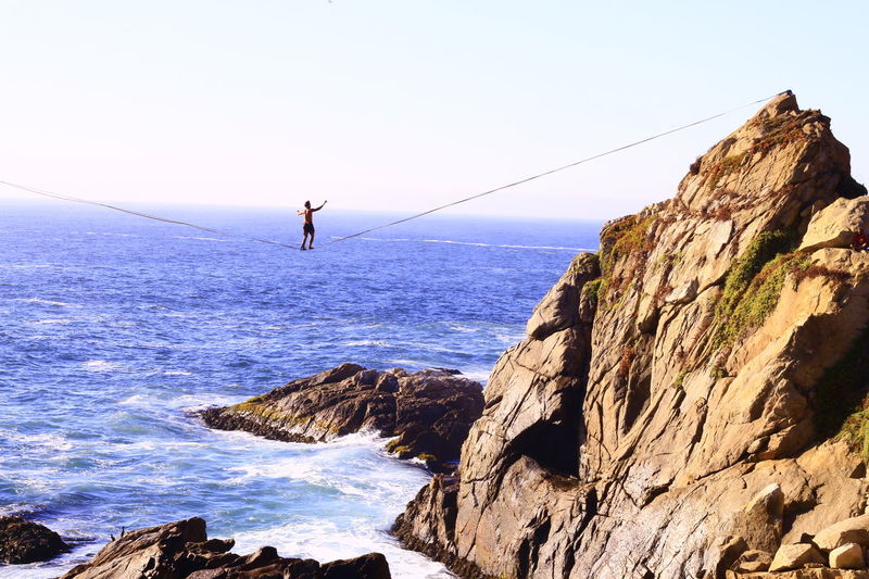 Resist Highline Longline Walking Walking The Line Beauty In Nature Sea Nature DayOutdoors One Person Sky Horizon Over Water Adventure Water Rock - Object Travel Destinations Clear Sky Lack Little To Reach
