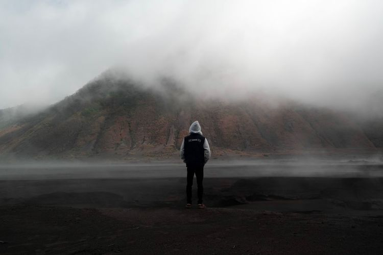 Rear view of man standing on landscape against sky during foggy weather