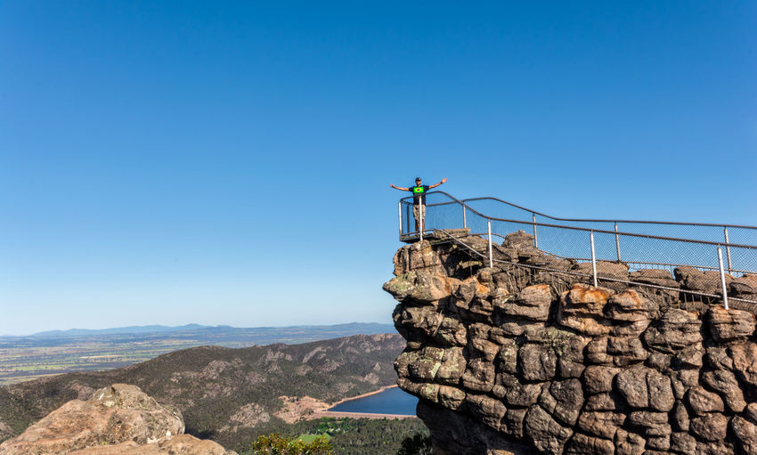 Man Standing At Observation Point On Cliff Against Sky