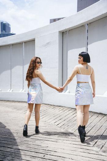 Rear view of lesbian women holding hands walking outdoors