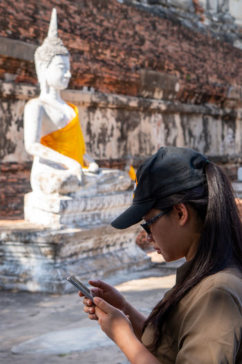 Side view of woman using mobile phone against buddha statue