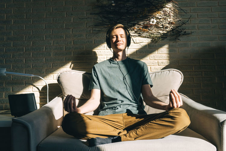 Full length of man meditating on sofa at home
