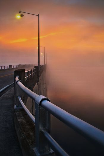 Railing by sea against sky during sunset