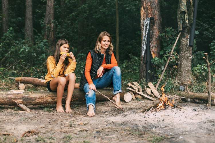 Full length of friends sitting on wood in forest