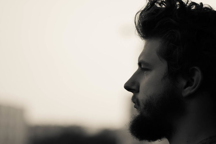 Close-up of thoughtful bearded man against sky