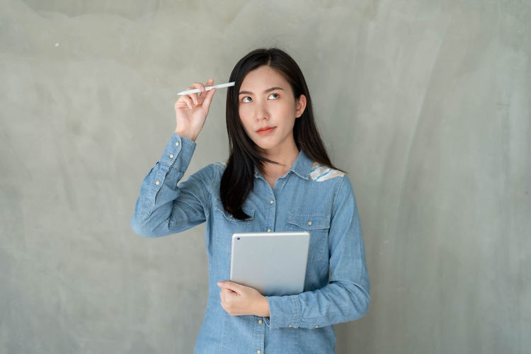 Portrait of a young woman holding smart phone while standing against wall