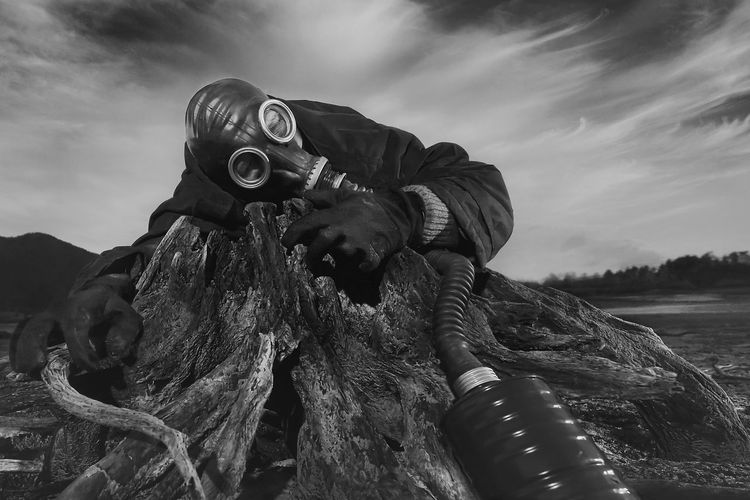 Low angle view of man with gas mask outdoors