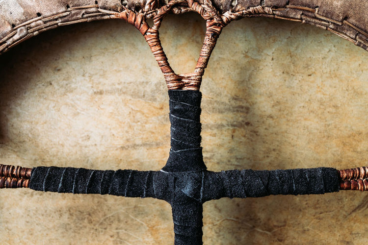 Close-up of tambourine with leather braided handle