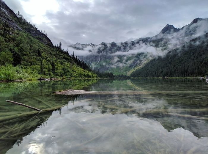 Scenic view of avalanche lake and mountains against sky in glacier national park