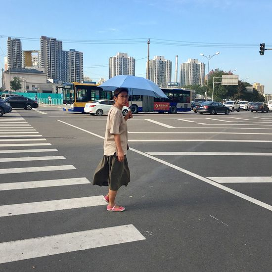 Young woman walking on road in city against clear sky