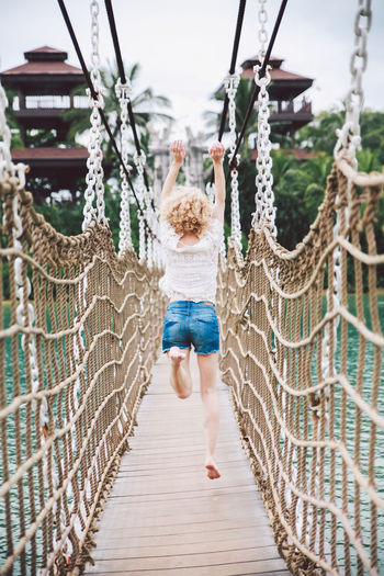 Rear view of young woman jumping over footbridge