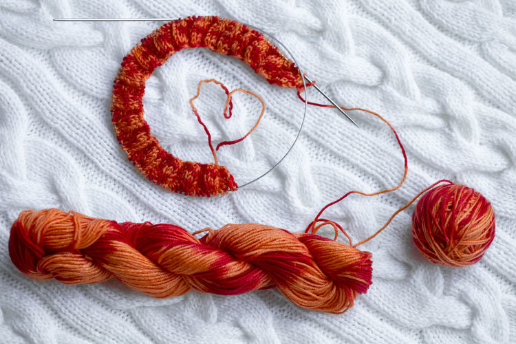 Knitting project in progress. A piece of knitting with a ball and a skein of red-orange color of sectional dyeing and knitting on the background of a white knitted plaid. Textile Wool Ball Of Wool Art And Craft Red Material Indoors  Craft Creativity Thread Close-up White Color Orange Color Sewing Needle Embroidery Knitting Knitting Needle Handmade Plaid Hobby Hobbies White White Background Still Life Pattern Art And Craft Red Knitting Sewing Heart Shape