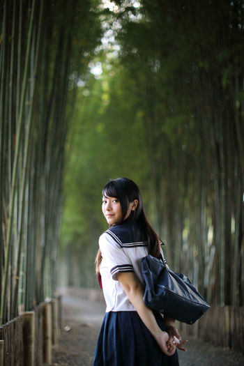 Rear view portrait of young woman in bamboo groove
