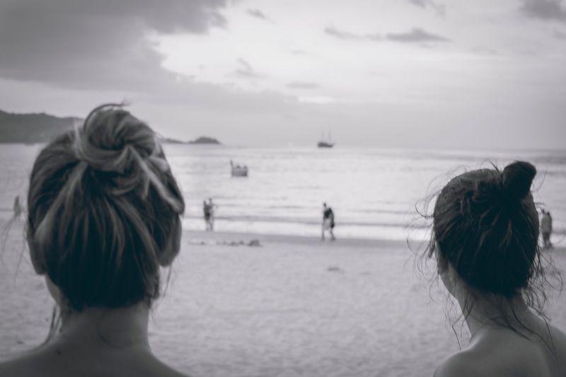 Rear view of women on beach against sky