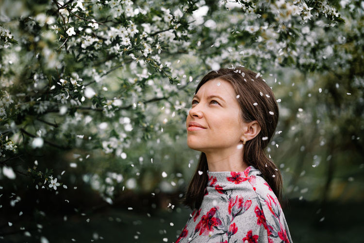Portrait of a beautiful young woman looking away by blooming tree in spring