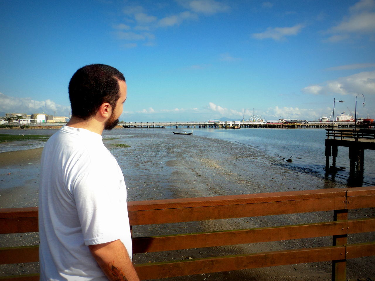 real people, water, sky, sea, cloud - sky, one person, leisure activity, lifestyles, rear view, casual clothing, outdoors, standing, nature, men, day, beach, beauty in nature, vacations, retaining wall, scenics, nautical vessel, young adult