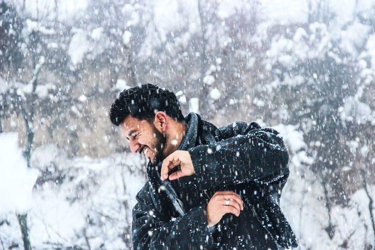 Playful man standing against trees during snowfall